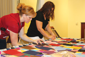 Jenn-e Heiner and Amy Forrest hand stitch a quilt that will be sent to Korea. A goal of 68 quilts has been set.