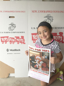 Emma Guillen, in front of a Toys For Tots drop off box, at Creative Shutters in Plano.