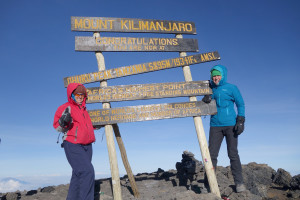 Christy Jones and her sister Corrie Crane stand atop the peak of Mount Kilimanjaro within the borders of Tanzania, situated close to the border of Kenya.