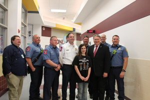 Madison Conner, shown center, was recognized at Draper Intermediate School last week for her life-saving efforts. Also pictured are Aaron Oleson, Captain Brandon Gibson, Jeff Pynes, Chief Brent Parker, Richard Hollien, Mayor Eric Hogue, Captain Casey Nash and Andrew Johnson.