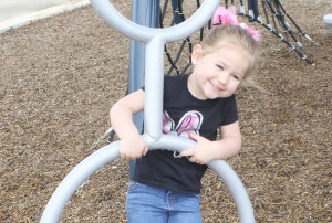Kenzlie Jenkins, 3, hangs onto a spiny circle last weekend at the Murphy Central Park playground.