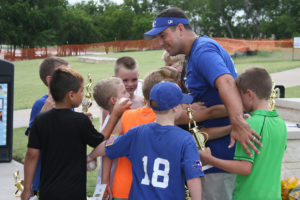Murphy resident and head coach of the Wylie Royals baseball team, Nick Cole, gets a group hug from his team during the end of season celebration at Murphy Central Park June 25.