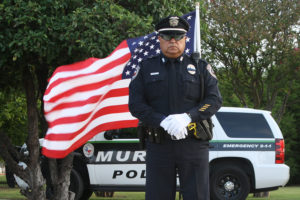 Murphy Police Officer Fred Mancias stands at attention in honor of the fallen Dallas Police Officers July 13. He stood at the corner of 544 and North Murphy Road from 7-8 a.m. in full dress uniform. The Exchange Club of Murphy provided the flags.