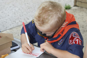 A little rain didn't stop Cooper Heise of Cub Scout Pack 1776 from writing a note to the troops on July 4 at Liberty Ridge Park in Murphy. The Exchange Club of Murphy hosted the event and handed out flags. Twenty four cards will be sent to the Veterans Hospital in Bonham.