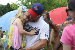 """Zoe Grall and father Jay Grall look at her theraphy Crunchie from Equest Therapeutic Horsemanship in Wylie last Saturday at the third annual """"When Life Gives You Lemons"""" event."""