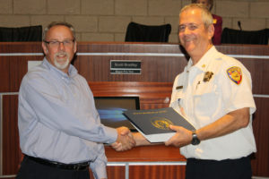 Murphy Mayor pro tem Scott Bradley presented outgoing Fire Chief Mark Lee was a flag flown at the state capital and a letter of thanks from State Rep. Jodie Laubenburg,